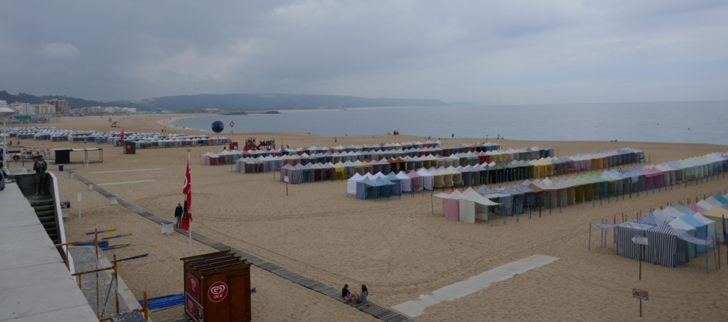 Rows and rows of colourful - and empty - tents on the beach at rainy Nazaré.