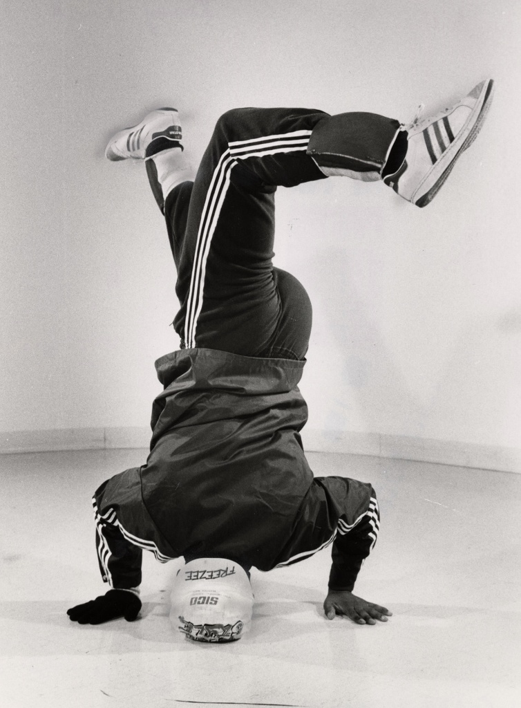 "Whole lotta breakin' going on, by Tony Brock, 1984. Exhibit caption reads, ""Nigel 'Sugar Pop' Walters, an 18 year-old student at North York's Earl Haig Collegiate, shows off his scissor kick during a headstand. A few days after this photo was taken, 'Breakdance '84,' Toronto's 'first ever high school street dance show,' was held at Riverdale Collegiate."" Image from Toronto Public Library under Toronto Star License."